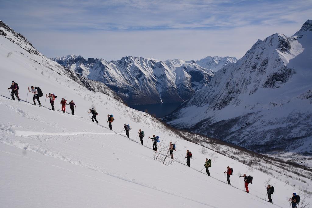 Snødekt fjellandskap og 17 personer som går opp en bratt bakke