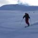 Et åpent og snødekt fjellandskap med godt kledde skikjørere som kjører slalom ned fjellsiden
