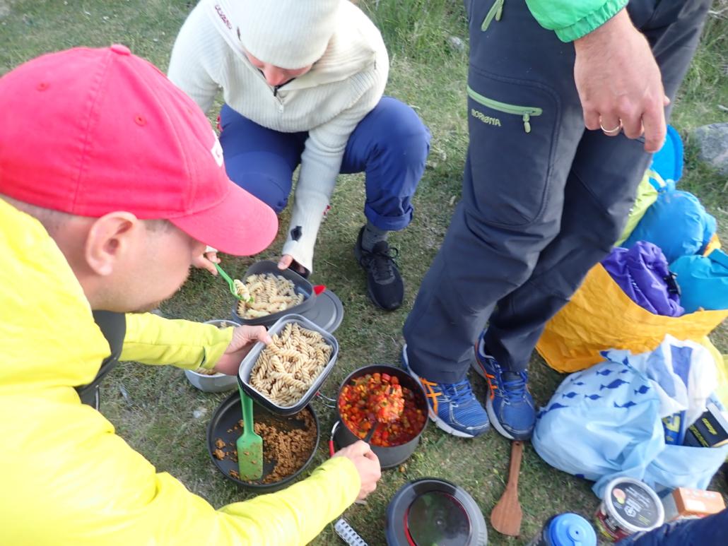 Tre mennesker som forsyner seg av pasta og gryterett fra stormkjøkken